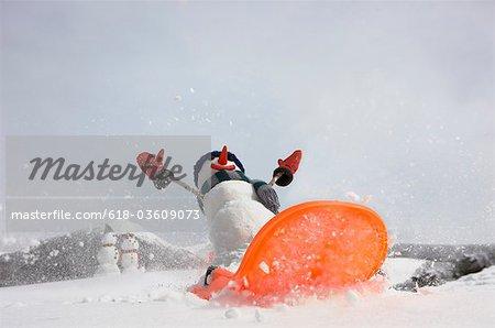 Snowman sledding downhill in snow