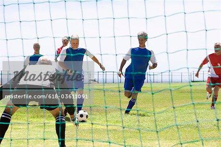 mature men kicking soccer ball towards goalkeeper, rear view