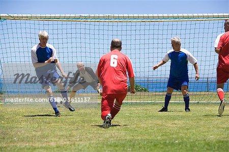 Mature soccer player kicking ball towards goal, rear view