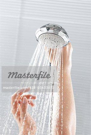 Woman taking shower, hands on shower head.