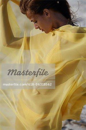woman in yellow bikini wrapped in yellow fabric