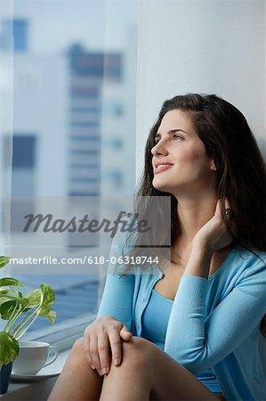 woman enjoying coffee, sitting near window