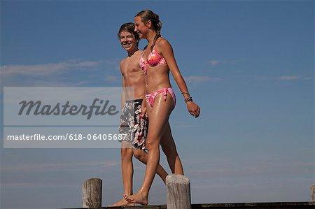 Young teenage couple walking along pier