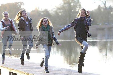 Girls skipping together on lake pier