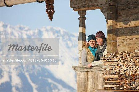 Couple on balcony of cabin at ski resort