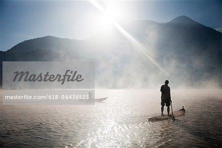 Man paddling iSUP on misty lake at sunrise