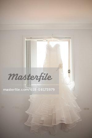 Wedding gown hanging in window
