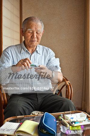 Diabetic man tests blood on finger