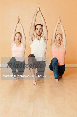 three people in yoga pose stock photo masterfile premium