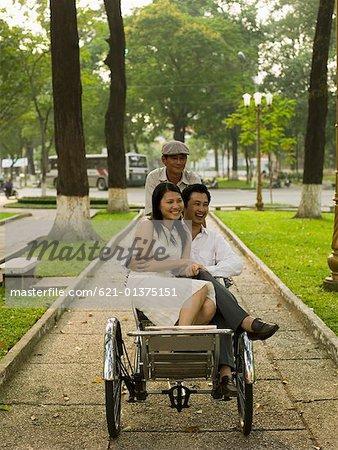 Couple riding in pedicab through park