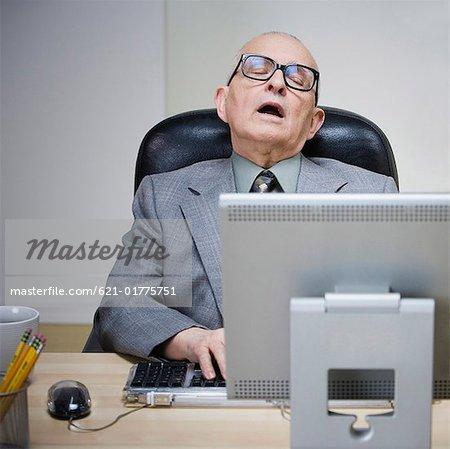 Senior Man Sleeping At Desk Stock Photo