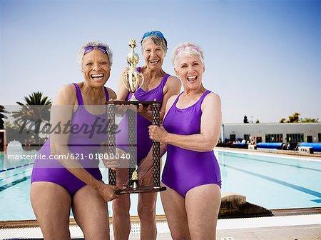 Smiling senior woman swim team holding trophy