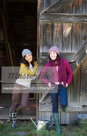 Portrait of friends by rustic barn