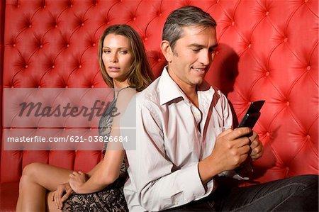 Couple back to back, man using phone