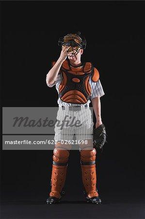 A baseball catcher standing and wearing helmet