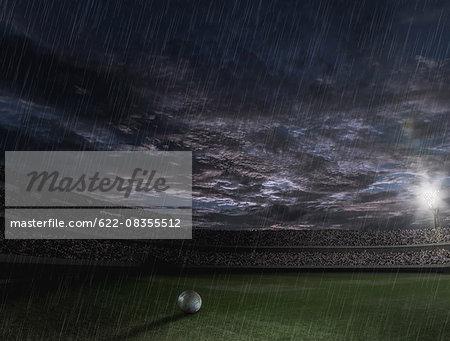 Soccer ball on the field on a rainy night
