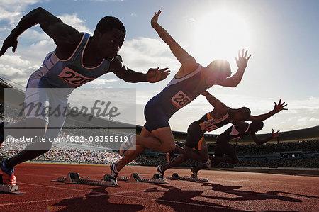 Athletes running on running track