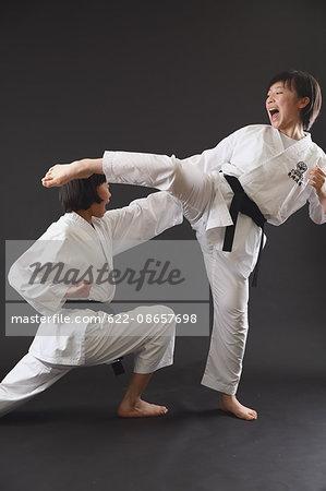 Japanese kids in karate uniform on black background