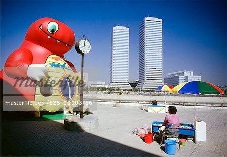 Man and woman sitting near an inflatable cartoon, Twin Towers, Osaka, Japan