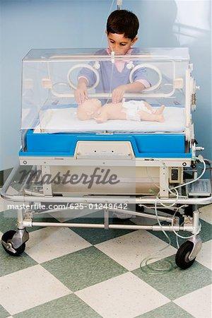 Boy touching a baby boy in an incubator
