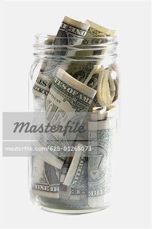Dollar bills squashed into a jar