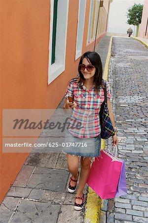 Young woman carrying shopping bags and using a mobile phone, Old San Juan, San Juan, Puerto Rico