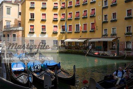 Gondolas docked in a canal near buildings, Venice, Italy