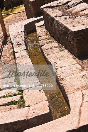 Water flowing through a stone's drain, Pisaq, Urubamba Valley, Peru
