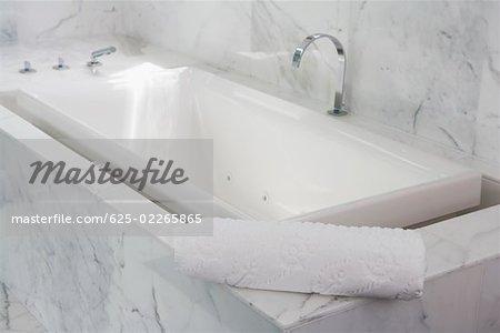 Towel on the ledge of a bathtub