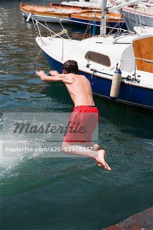 Rear view of a boy jumping in water, Borgo Marinaro, Bay of Naples, Naples, Naples Province, Campania, Italy