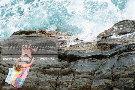 High angle view of a woman lying on cliff, RioMaggiore, Cinque Terre, Italian Riviera, Cinque Terre National Park, Vernazza, La Spezia, Liguria, Italy