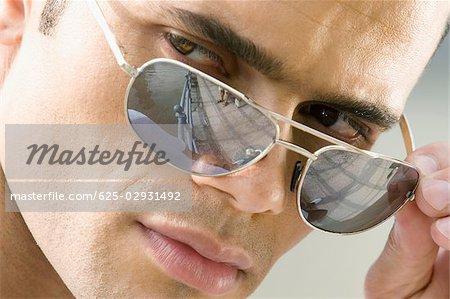 c9df0f1770e6 Close-up of a mid adult man peeking over his sunglasses - Stock Photo