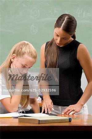 Female Teacher Teaching A Schoolgirl In A Classroom Stock Photo