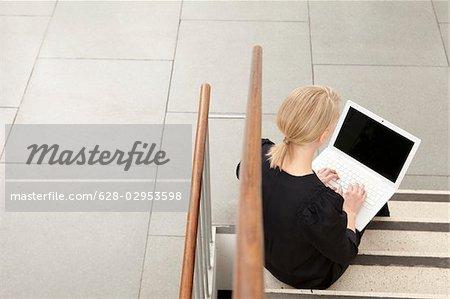 Woman using laptop on stairs, Munich, Bavaria, Germany