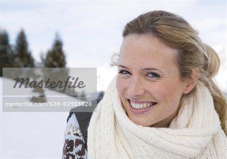 Happy woman wearing scarf in winter landscape
