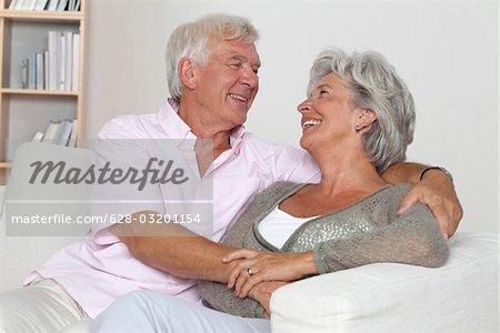 Senior couple hugging on sofa