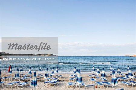 Sun loungers and sunshades on the beach, Sardinia, Italy