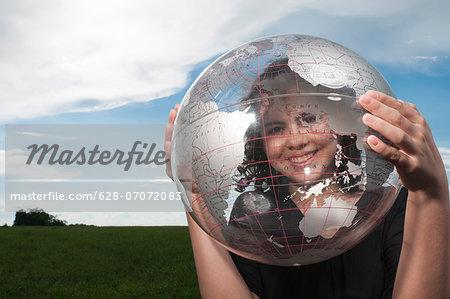 Girl looking through transparent globe outdoors