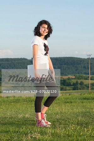 Girl walking with laptop in meadow