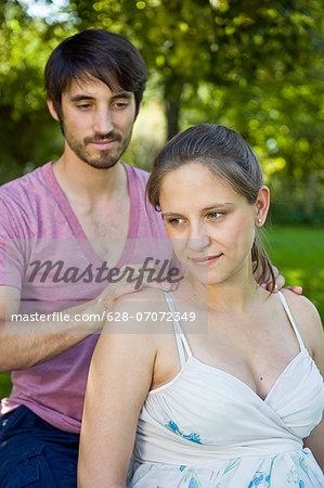 Man massaging pregnant woman's shoulders