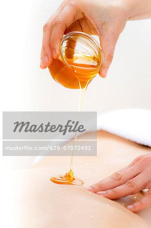 Masseuse pouring honey on females' back