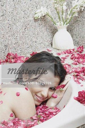 Portrait of a young woman lying in a bathtub