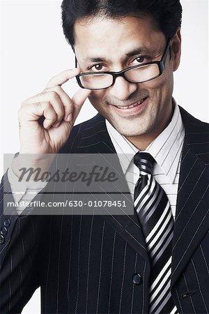 Portrait of a businessman peeping over his eyeglasses