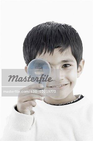 Portrait of a boy holding a light bulb