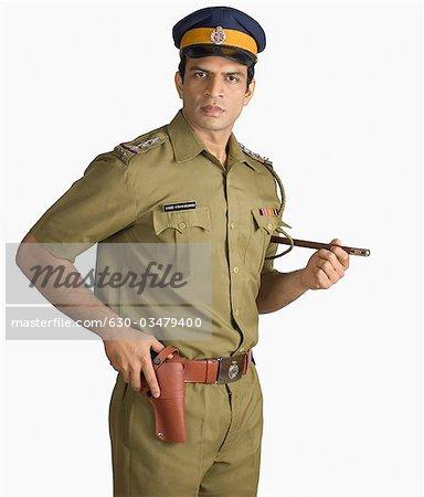 Portrait of a policeman holding a handgun Stock Photo Masterfile