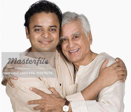 Portrait of a senior man hugging his son