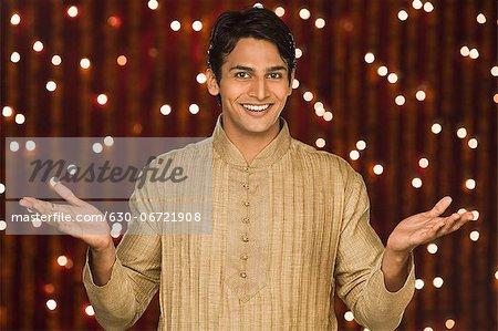 Man shrugging in front of Diwali decoration