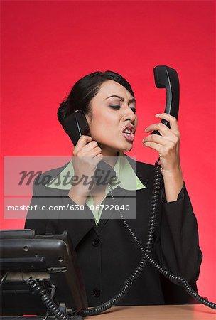 Businesswoman using multiple landline phones and shouting