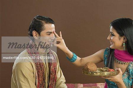 Woman applying tilak on her brother's forehead at Raksha Bandhan festival