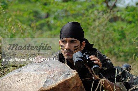 Soldier hiding behind a rock with binoculars